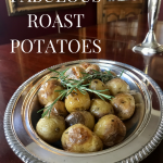 Silver dish with roasted potatoes sitting on dining room table.