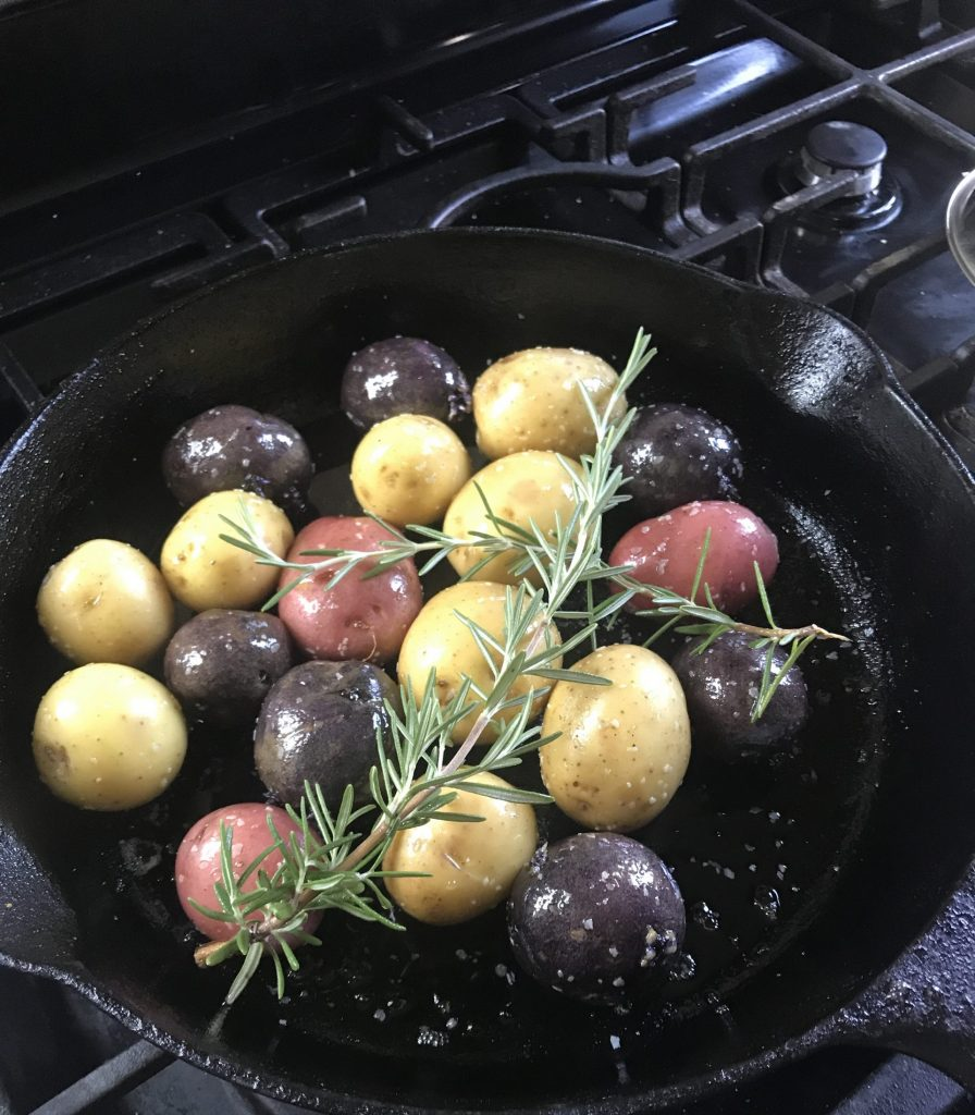 Potatoes in cast iron skillet with rosemary sprigs