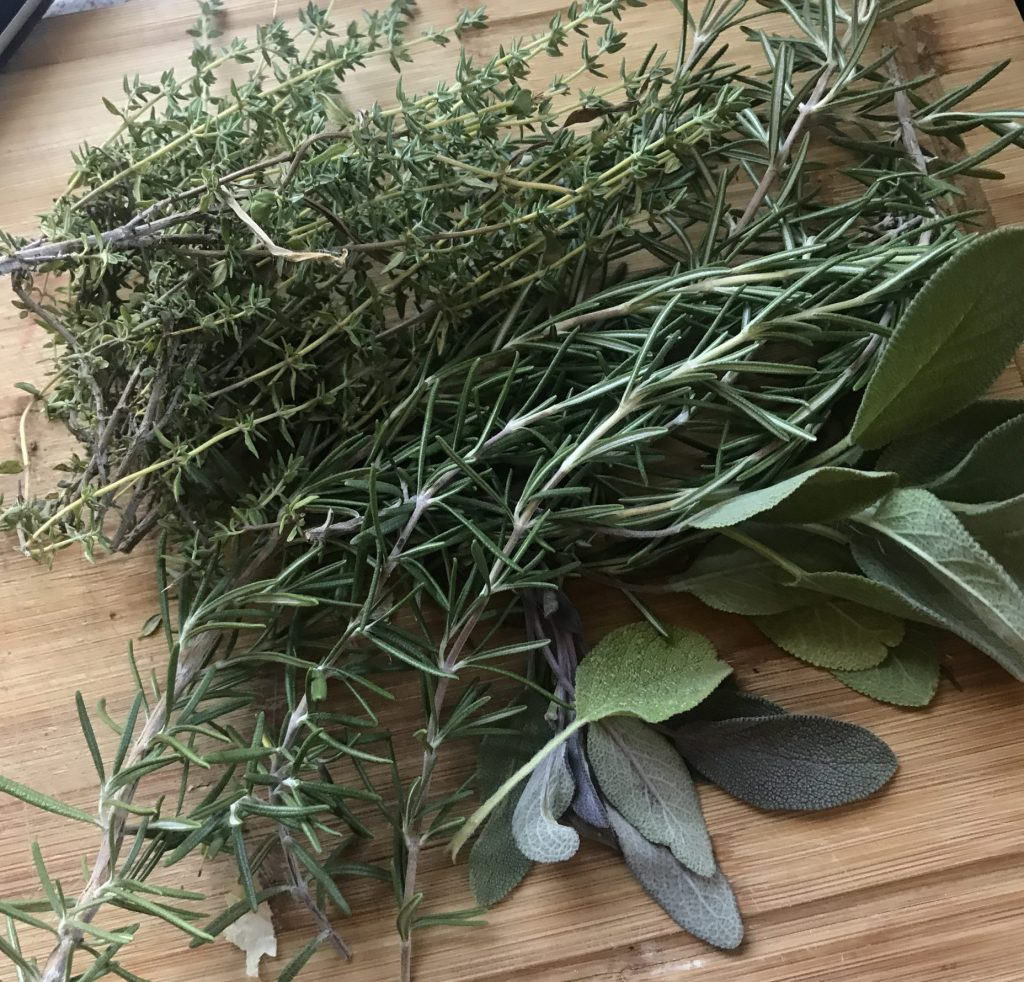 Pile of fresh thyme, rosemary and sage on a wooden cutting board
