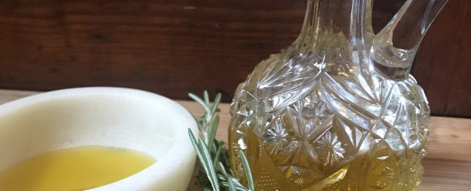 Cut glass cruet with oil in it and a small dish with oil, near spring of herbs