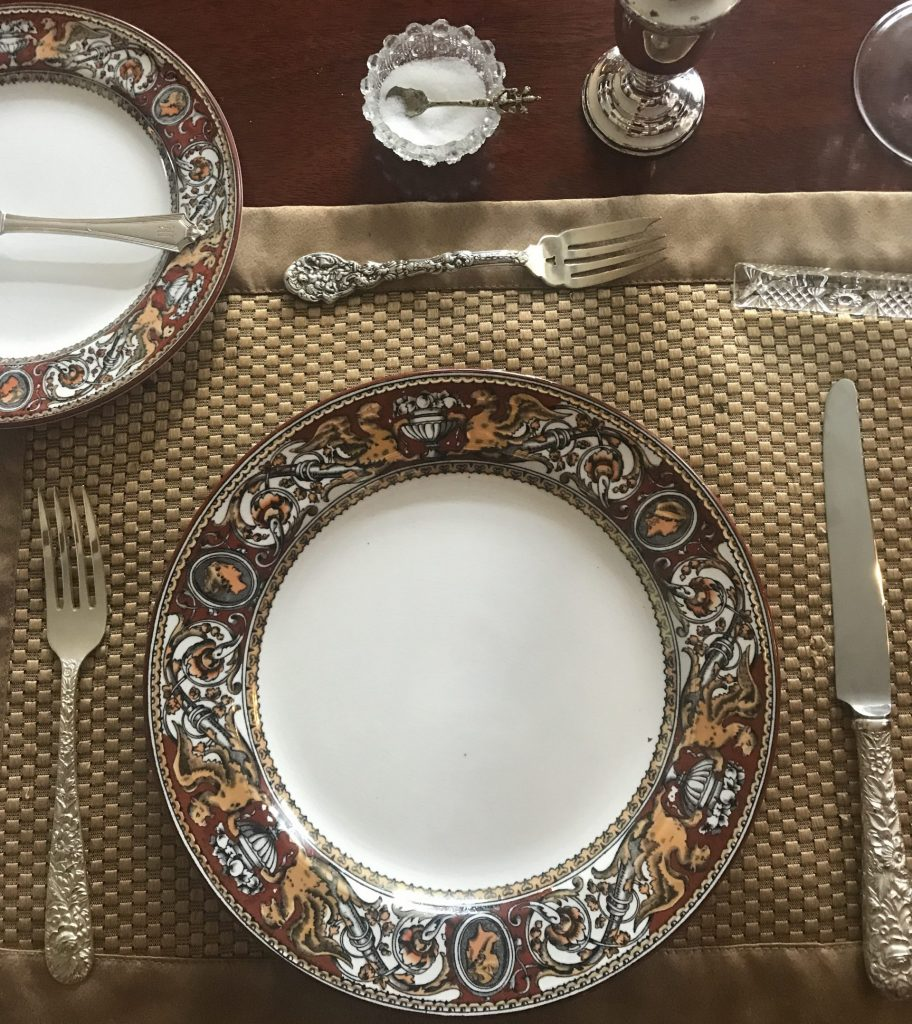 place setting showing a plate with silver flatware in coordinating but unmatched patterns.
