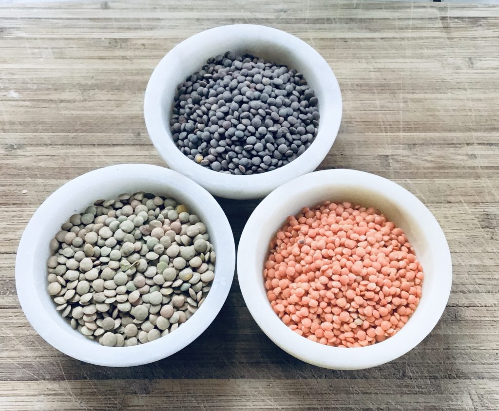green, brown and red lentils in dishes
