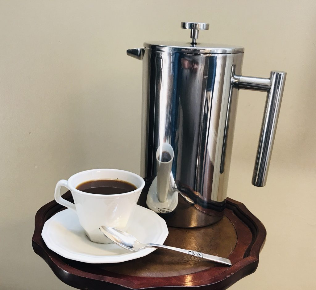 white coffee cup and saucer with silver spoon and large steel French press